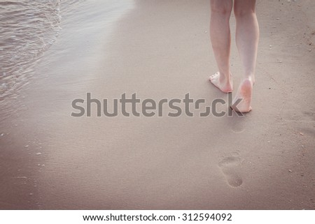 Beach travel alone - woman walking alone on sand beach leaving footprints in the sand Closeup detail of female feet and golden sand background