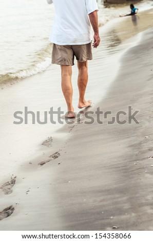 Beach travel - man walking on sand beach leaving footprints in the sand. Closeup detail of male feet - stock photo