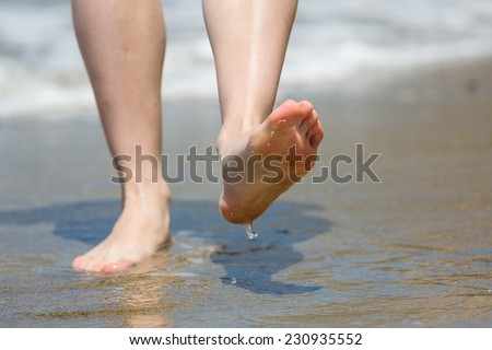Beach travel - woman walking on sand beach