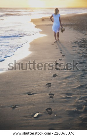 Beach travel - woman walking on sand beach leaving footprints in the sand.  - stock photo