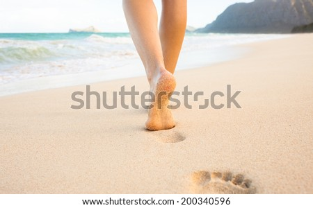 Beach travel - woman walking on sand beach leaving footprints in the sand. Closeup detail of female feet and golden sand on Maui, Hawaii, USA. - stock photo