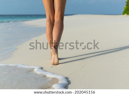 Beach travel - woman walking on sand beach leaving footprints in the sand. Closeup detail of female feet - stock photo