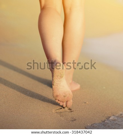Beach travel - woman walking on sand beach leaving footprints in the sand. Closeup detail of female feet and golden sand beach  - stock photo