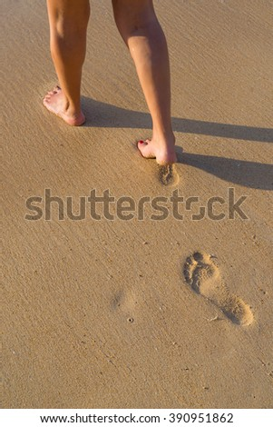 Beach travel - woman walking on sand beach leaving footprints in the sand. Closeup detail of female feet and golden sand