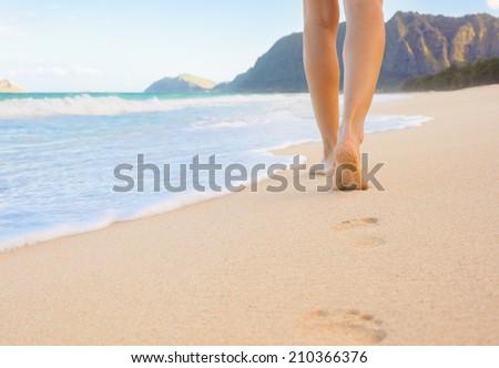 Beach travel - woman walking on sandy beach leaving footprints in the sand. - stock photo
