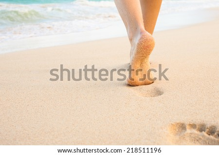 Beach travel - woman walking on sandy beach leaving footprints in the sand. Closeup detail of female feet and golden sand on beach in Hawaii - stock photo