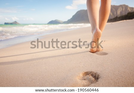 Beach travel - young girl walking on sandy beach leaving footprints in the sand, Hawaii, USA. - stock photo