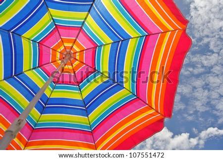 Beach umbrella and blue sky on a summer day - stock photo
