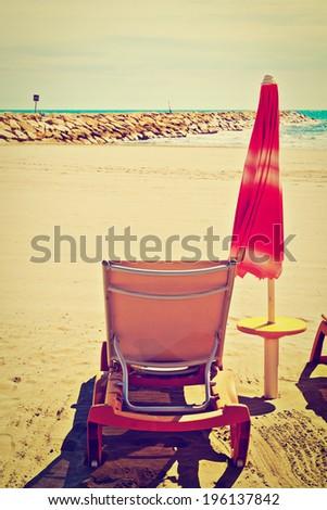 Beach Umbrella and Sun Bed in the Low Season, Retro Effect - stock photo