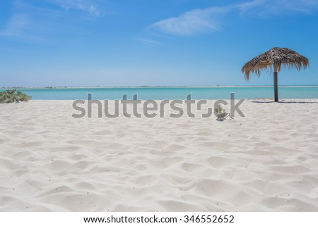 Beach Umbrella made of palm leafs on the background of an exotic beach in Cayo Largo - stock photo