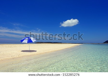Beach umbrella on a sunny beach with the blue sea in the background.