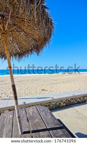 Beach Umbrella Palm Leafs with Picnic Table - stock photo