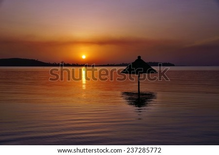 Beach umbrella silhouette in water on sunset from Bugala Island, Ssese Islands, Uganda  - stock photo