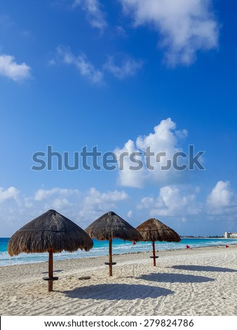 Beach umbrellas along Caribbean sea coast, Cancun on rare cloudy day - stock photo