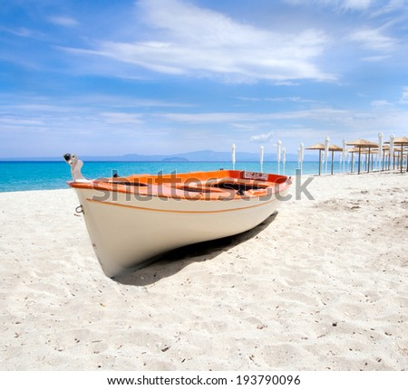 Beach umbrellas and a boat on a beautiful  sandy beach - stock photo