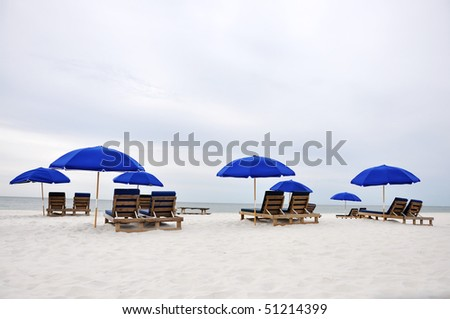 Beach umbrellas and chairs on deserted beach. - stock photo