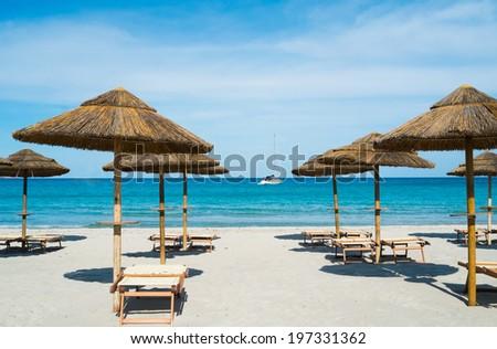 Beach umbrellas and deck chairs in Porto Giunco beach, Villasimius, Sardinia, Italy - stock photo