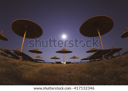 Beach Umbrellas at Moon Light Wallpaper - stock photo