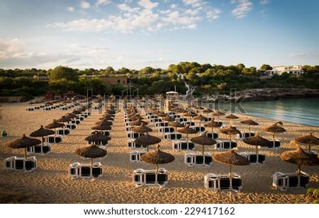 Beach umbrellas at sunset in Mallorca - stock photo