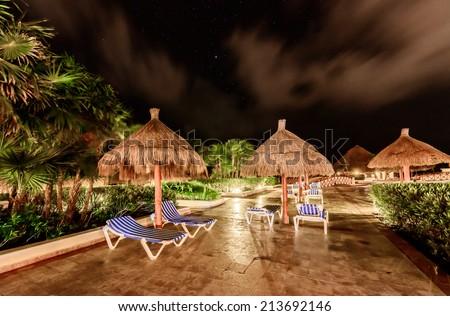 Beach umbrellas at swimming pool at  luxury caribbean resort at night, dawn time. Bahia Principe, Riviera Maya, Mexican Resort. - stock photo