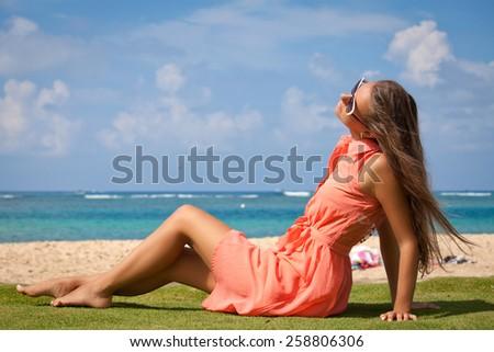 Beach vacation - beautiful carefree woman in summer dress relaxing on Waikiki beach, Honolulu city, Oahu Island, Hawaii, USA  - stock photo