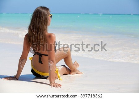 Beach vacation beautiful dreaming woman enjoying summer holiday on perfect ocean tropical destination. Girl sitting on white sand beach getaway. Summer luxury vacation. - stock photo