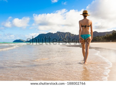 Beach vacation. Beautiful woman in sun hat and bikini walking on the beach in Hawaii, USA. - stock photo