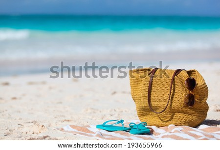 Beach vacation close up. Straw bag, sun glasses, towel and flip flops on a tropical beach  - stock photo