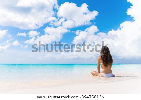 Beach vacation dream woman enjoying summer holiday on dreamy perfect ocean tropical destination. Person sitting from the back alone on deserted white sand beach getaway. - stock photo