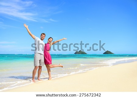 Beach vacation happy carefree couple arms raised. Winning couple with arms up showing happiness and fun on beach with pristine turquoise water on Lanikai beach, Oahu, Hawaii, USA with Mokulua Islands. - stock photo