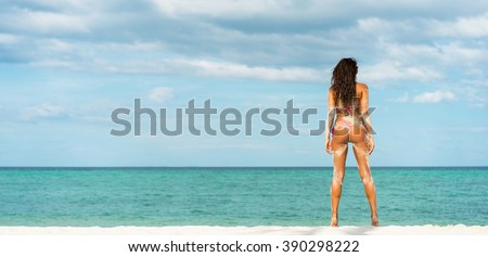 Beach vacation. Hot beautiful woman in bikini standing and  enjoying looking view of beach ocean on hot summer day. Banner - stock photo