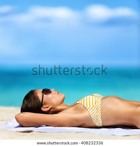 Beach vacation woman in bikini wearing sunglasses. Young lady sunbathing relaxing. Sexy young adult wearing eyewear for sun protection lying down on towel on sand tanning. Skincare UV sun care. - stock photo