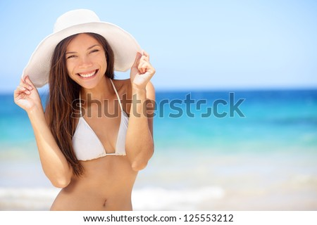 Beach vacation woman in sun smiling happy on summer holidays on tropical beach. Beautiful multiethnic asian chinese / caucasian bikini model wearing beach hat. - stock photo