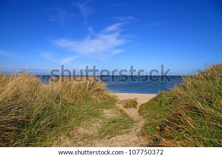 Beach view over dunes with sand water and sky - stock photo