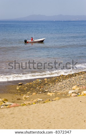 beach view with one boat and men in red - stock photo