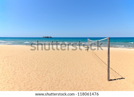 Beach Volleyball net on sandy beach with sea and blue sky in the background - stock photo