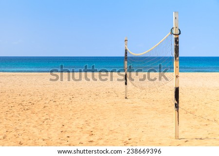 Beach Volleyball on sandy beach with sea and blue sky in the background - stock photo