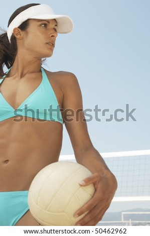 Beach volleyball player in bikini holding volleyball outdoors - stock photo