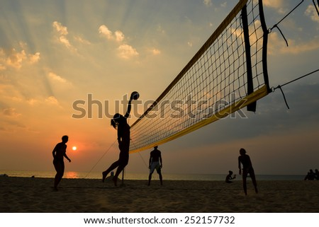 Beach volleyball silhouette at sunset , motion blurred - stock photo