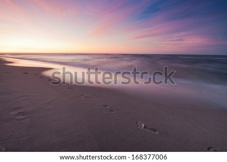 Beach, wave and footsteps at seascape - stock photo