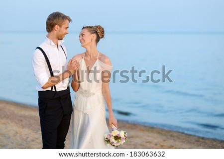 Beach wedding: bride and groom hugging by the sea