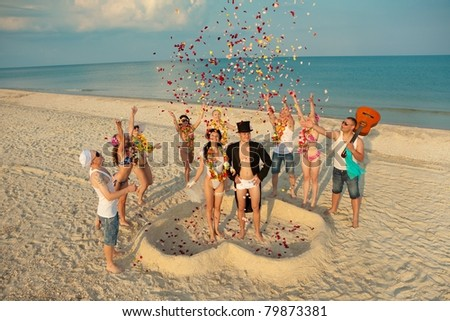 Beach wedding of happy newlywed couple around their friends - stock photo