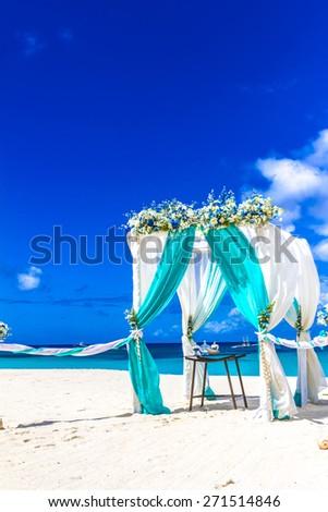 beach wedding venue, wedding setup, cabana, arch, gazebo decorated with flowers - stock photo