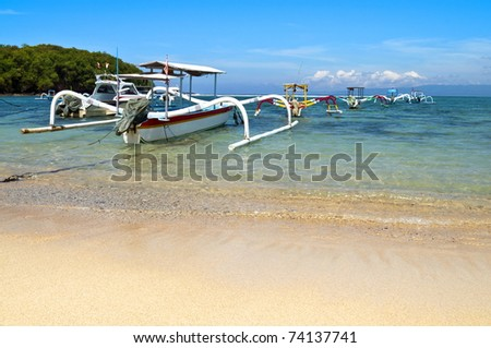 Beach with anchored traditional boats in Gili island - stock photo