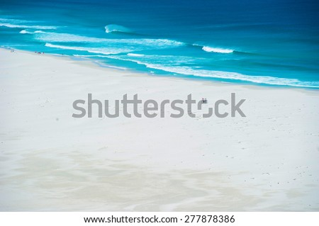 Beach with bright blue turquoise water, white sand and waves shot pictured from above. - stock photo