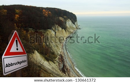 Beach with chalk cliff at island Ruegen  Mecklenburg-Vorpommern, Germany and warning sign - stock photo