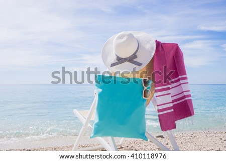 beach with deck chair, towel, bag,  hat and sunglasses - stock photo