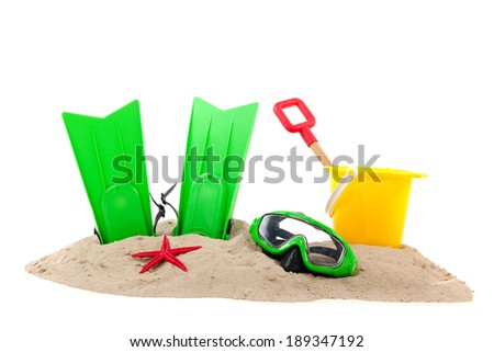 Beach with green diving equipment and yellow bucket - stock photo