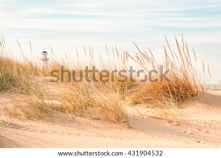 Beach with lighthouse in the background - stock photo