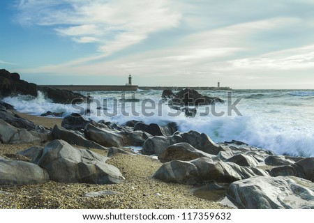 Beach with rocks and a cloudy sky. - stock photo